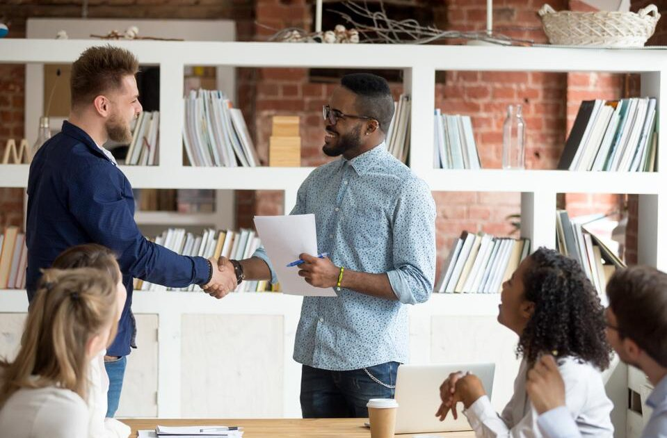 Smiling black CEO handshake Caucasian employee greeting with successes