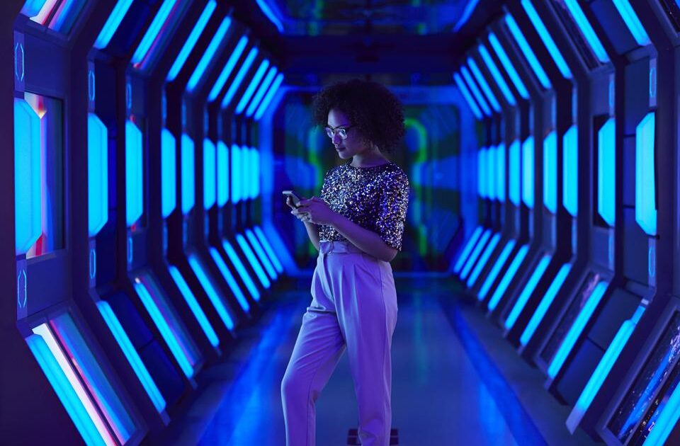 Young business woman looking at smartphone in spaceship like corridor