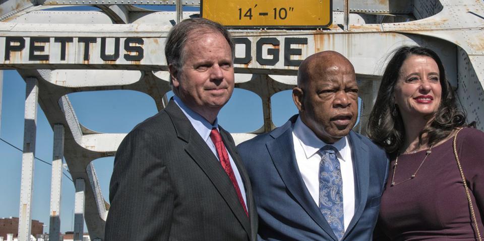 Senator Doug Jones stands on Edmund Pettus Bridge with Rep. John Lewis